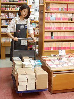 文学売り場用の台車に積まれた本を運ぶ。