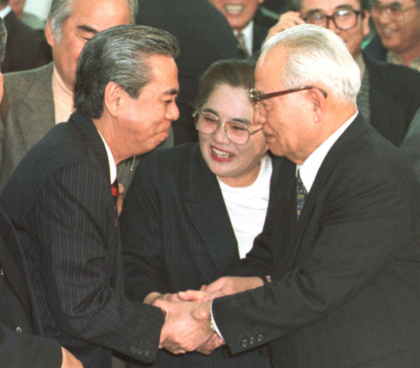 1998年2月、初当選を決め、比嘉鉄也・前名護市長(右)と握手する岸本建男 ©共同通信社