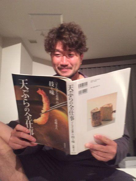 天ぷらの本を熱心に読む石川歩 ©梶原紀章