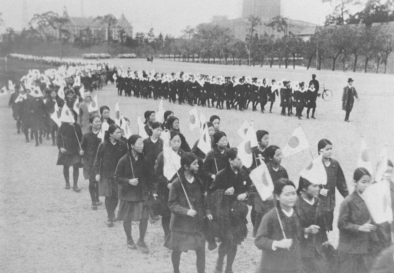 昭和5(1930)年、教育勅語発布40年式典で旗行列する私立高女の生徒たち ©共同通信社