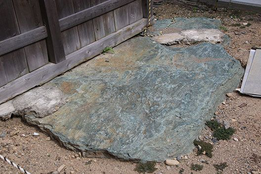 ちなみに囲い塀の下にある青い石は紀の川流域特有の緑泥片岩。縄文時代のものだという