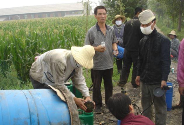 畑で農薬を調合する農民たち ©高橋五郎