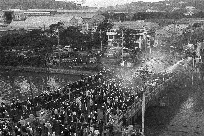 寄港に反対し角材を手に平瀬橋を進む学生に放水、催涙ガスで阻止しようとする警官隊 ©時事通信社